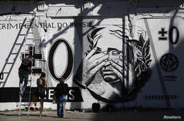 People stand in front of graffiti mocking the Brazilian currency note, the real, in downtown Rio de Janeiro, Brazil July 31, 2014.