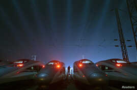 FILE - A worker stands among CRH (China Railway High-speed) Harmony bullet trains at a high-speed train maintenance base in Wuhan, Hubei province March 9, 2015. China is poised to embark on a fresh round of industrial consolidation, as part of a swee
