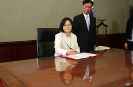 Taiwan's President Tsai Ing-wen signs her first document at her new desk following the inauguration ceremony at the Presidential Office in Taipei, Taiwan May 20, 2016.