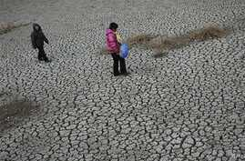 People walk on a dried up pond at Hanzhuang village in Tangyin county in central China's Henan province (File Photo)