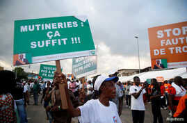 "A partisan of the ruling party RDR (Rally of the republicans) holds a placard during a rally against the mutiny close to the military headquarters in Abidjan, Ivory Coast, May 13, 2017. The placard reads, ""Mutinies: it's enough""."