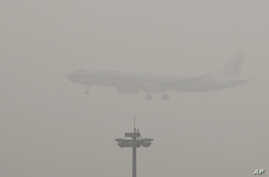 An Air China passenger plane prepares to land at the Beijing Capital International Airport as the capital of China through heavy smog on Wednesday, Dec. 21, 2016.