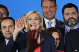 FILE - French far right leader Marine Le Pen, center, waves on stage next to other populist leaders at the end of a May Day meeting in Nice, south of France, May 1, 2018.