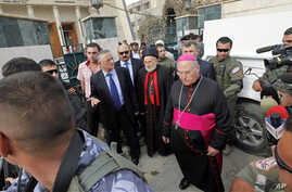 Iraqi Christian lawmaker, Younadem Kana, center left, Iraq's top Catholic prelate, Chaldean Cardinal Emmanuel III Delly, center, and Bishop Shlimone Wardoni, center right, are seen outside Our Lady of Deliverance church the morning after its congrega