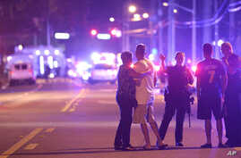 Police officers direct family members away from a fatal shooting at Pulse Orlando nightclub in Orlando, Fla., June 12, 2016.