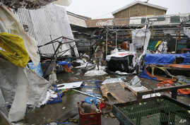 Residents walk along destroyed stalls at a public market after Typhoon Mangkhut barreled across Tuguegrao city in Cagayan province, northeastern Philippines, Sept. 15, 2018.