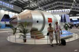 Visitors sit besides a model of Chinese made Tiangong 1 space station at the 8th China International Aviation and Aerospace Exhibition, known as Airshow China 2010, in Zhuhai city, south China, Guangdong province (2010 File)