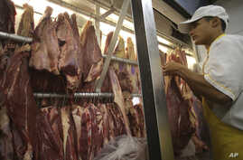An employee works in a butcher shop in Brasilia, Brazil, Monday, March 20, 2017.