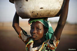 FILE - A Ghanaian girl waits to sell water in the northern city of Tamale.