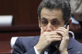 FILE - In this Dec.11, 2009 file photo, then French President Nicolas Sarkozy makes a phone call during a EU summit at the European Council building in Brussels.