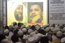 Portrait of Osama Bin Laden and U.S. President Barack Obama are projected on a screen during a prayer for the slain al-Qaida leader at the headquarters of hardline group Islam Defenders Front (FPI) in Jakarta, Indonesia, May 4, 2011