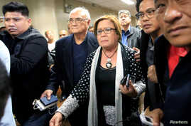 Philippine Senator Leila de Lima is escorted by the Senate's security personnel after a Regional Trial Court ordered her arrest, at the Senate headquarters in Pasay city, metro Manila, Philippines. Feb. 23, 2017.