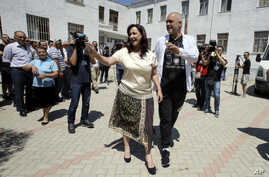 Albanian Prime Minister and leader of the Socialist party Edi Rama, right, and his wife Linda wave to supporters before casting their ballots at a polling station in Tirana outskirts, June 25, 2017.