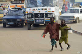 FILE - Two students beg to meet the daily quota imposed by their teacher in a neighborhood of Dakar, Senegal, Aug. 31, 2010. A mobile videogame was created which aims to raise awareness of the tens of thousands of children in Senegal who are forced t