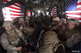 U.S. Marines are seen on board a helicopter at Kandahar air base upon the end of operations for the Marines and British combat troops in Helmand province, Oct. 27, 2014.