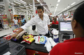 A customer puts his finger on a fingerprint scanner as part of the process to buy groceries at Bicentenario, a state-run supermarket, in Caracas, Venezuela, Sept. 25, 2014.