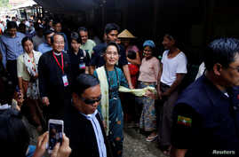 Myanmar State Counselor Aung San Suu Kyi talks to people as she visits an IDP camp
