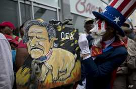 A protester mocking Uncle Sam holds a painting of OAS leader Luis Almagro at a rally against the United States and possible OAS sanctions, in Caracas, Venezuela, March 28, 2017, as OAS diplomats meet in Washington.