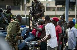 African Union Misca forces from Cameroon carry a wounded man as angry youth set up barricades throughout the town,  May 29, 2014 in Bangui, Central African Republic.