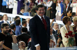 Turkey's Foreign Minister Ahmet Davutoglu greets supporters during a meeting of the ruling AK Party (AKP), in Ankara August 27, 2014.