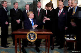 President Donald Trump, surrounded by business leaders and administration officials, gives the pen to Lockheed Martin CEO Marillyn Hewson after signing a memorandum on intellectual property tariffs on high-tech goods from China, at the White House, M