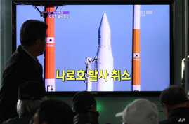 People watch a TV broadcasting a report about the cancellation of a launch of the Korea Space Launch Vehicle-1, at Seoul Railway Station in Seoul, South Korea, Nov. 29, 2012.