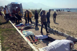 Turkish rescue workers and medics work next to the bodies of migrants laid out near an ambulance in Kusadasi, Turkey, March 24, 2017.