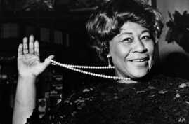 """FILE - In this Feb. 22, 1968 file photo, American jazz singer Ella Fitzgerald swings her necklace as she arrives at the Carlton Theatre in London, England. The National Portrait Gallery is putting up a photograph of Fitzgerald, often referred to as """""""