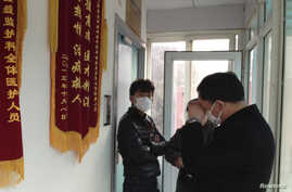 Friends of human right activist Cao Shunli stand in front of an intensivae care unit where Cao is hospitalized as they are not allowed to go inside of the unit at a hospital in Beijing, China, Mar. 1, 2014.