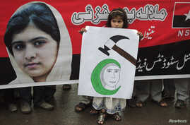 A girl holds a placard next to an image of schoolgirl Malala Yousufzai, who was shot on October 9 by the Taliban, during a rally organized by National Students Federation (NSF) in Lahore October 15, 2012. Yousufzai, 14, who was shot by Taliban gunmen