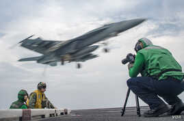 Mass Communication Specialist 2nd Class Sean Castellano, from Colorado Springs, Colo., records video footage on the flight deck of the Nimitz-class aircraft carrier USS Carl Vinson in the western Pacific region, May 23, 2017.