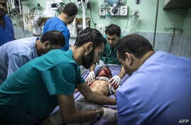 Shahed Qishtah, a nine-year-old Palestinian girl, receives medical care at an emergency room of the Kamal Adwan hospital in Beit Lahia after she was injured in an Israeli strike while playing on July 22, 2014 in the northern Gaza Strip.