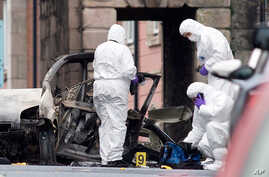 Police forensic officers inspect the aftermath of a suspected car bomb explosion in Derry, Northern Ireland, Jan. 20, 2019.