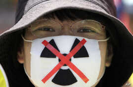 An anti-nuclear protester waits to begin a march through downtown Tokyo, Japan, July 16, 2012.
