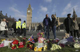 People view floral tributes to victims of Wednesday's attack outside the Houses of Parliament in London, March 24, 2017. On Thursday authorities identified a 52-year-old Briton as the man who mowed down pedestrians and stabbed a policeman to death o