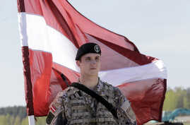 FILE - A Latvian soldier is seen holding a national flag as he waits to greet US soldiers arriving for exercises, at the airport in Riga April 24, 2014.