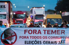 """Protestors block the Presidente Dutra highway during a strike against Brazilian Social Welfare reform project from government, in Sao Jose dos Campos, Brazil March 15, 2017. The banner reads: """"Out, Temer. Out, all corrupt. Elections now."""""""