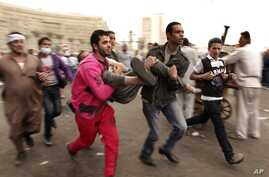 Protesters rush a wounded comrade to a field hospital in Tahrir Square, Cairo, Egypt, November 23, 2012.