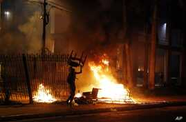 A protester carries a chair to a fire outside the Congress building during clashes between police and protesters opposing a constitutional amendment that would allow the election of a president to a second term, in Asuncion, Paraguay, March 31, 2017....