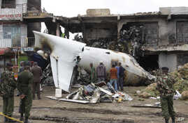 Soldiers look at the wreckage of the Fokker 50 cargo plane after it crashed, killing the four crew members aboard, shortly after takeoff at Kenyatta International Airport, Nairobi, Kenya, July 2, 2014.