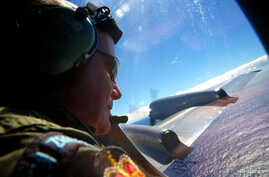 Seargent Trent Wyatt looks out an observation window aboard a Royal New Zealand Air Force (RNZAF) P3 Orion maritime search aircraft as it flies over the southern Indian Ocean looking for debris from missing Malaysian Airlines flight MH370.