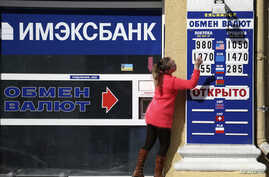 An employee changes rates on a notice board at a currency exchange in Simferopol, March 17, 2014.