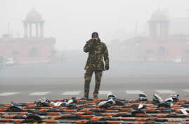 An Indian Air Force soldier drinks tea as he stands guard next to rifles during a break at the rehearsal for the Republic Day parade on a cold winter morning in New Delhi, India, Dec. 26, 2018.