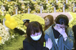 Relatives of a passenger aboard the sunken ferry Sewol weep as they pay tribute to the victims of the ship at a group memorial altar in Ansan, South Korea, May 4, 2014.