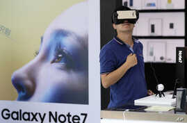 China South Korea Samsung Battery Fires: FILE - In this Wednesday, Sept. 7, 2016, file photo, a man tries out the Samsung VR using their latest Galaxy Note 7 smartphone at a roadshow outside a shopping mall in Beijing.