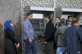 Employees wait in line in at a cash machine to receive their monthly salaries in Gaza City, April 5, 2017. The cash-strapped Palestinian Authority said it has slashed the salaries of some 50,000 government employees in the Gaza Strip.