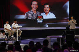 "Indonesia's presidential candidate Joko ""Jokowi"" Widodo (R) speaks during a televised debate with his opponent Prabowo Subianto and Hatta Rajasa (L) in Jakarta, July 5, 2014."