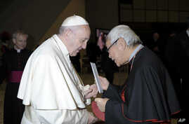 In this Jan. 10, 2018 photo made available the Vatican newspaper L'Osservatore Romano, retired archbishop of Hong Kong Cardinal Joseph Zen hands a letter to Pope Francis at the end of his weekly general audience.