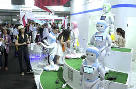 In this image taken from video, visitors look at iPal robots during the Shanghai CES electronic show in Shanghai, China, June 8, 2017. More than 50 companies are showcasing a new generation of robots at this week's Shanghai CES electronics show, most