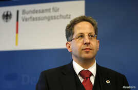 FILE - President of Germany's intelligence agency Verfassungsschutz Hans-Georg Maassen listens during a visit by German Interior Minister Thomas de Maiziere at the Federal Office for the Protection of the Constitution in Cologne.